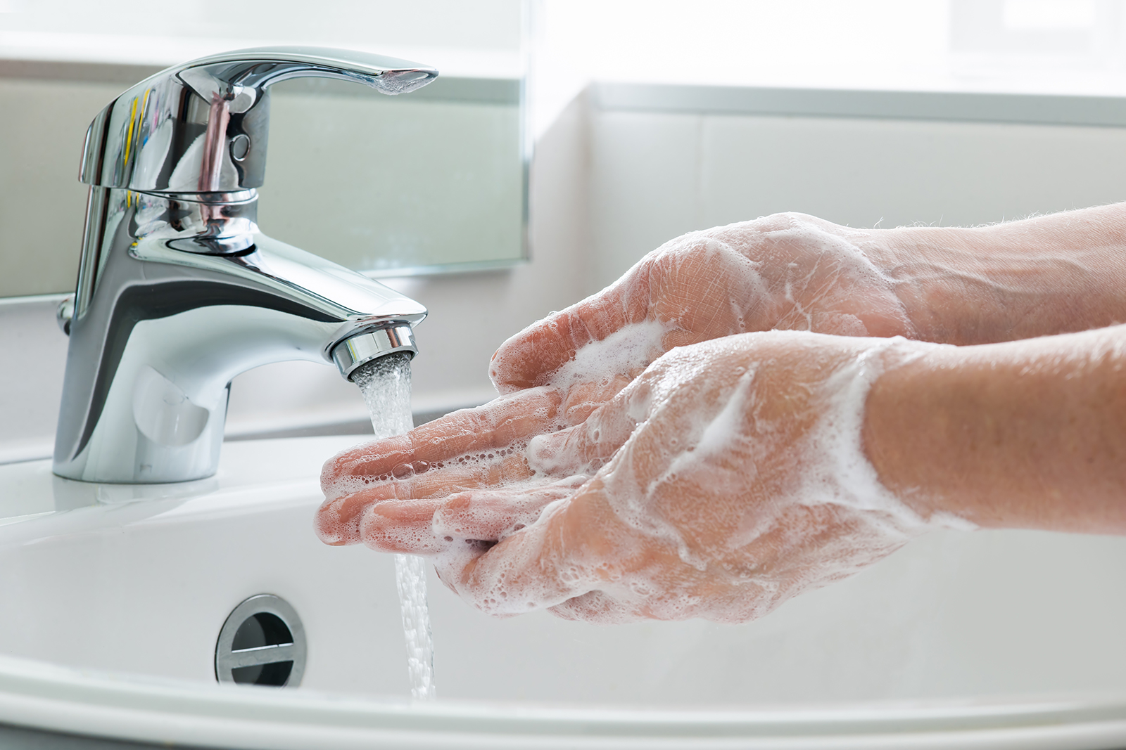 Soapy hands being washed under a sink with running water.