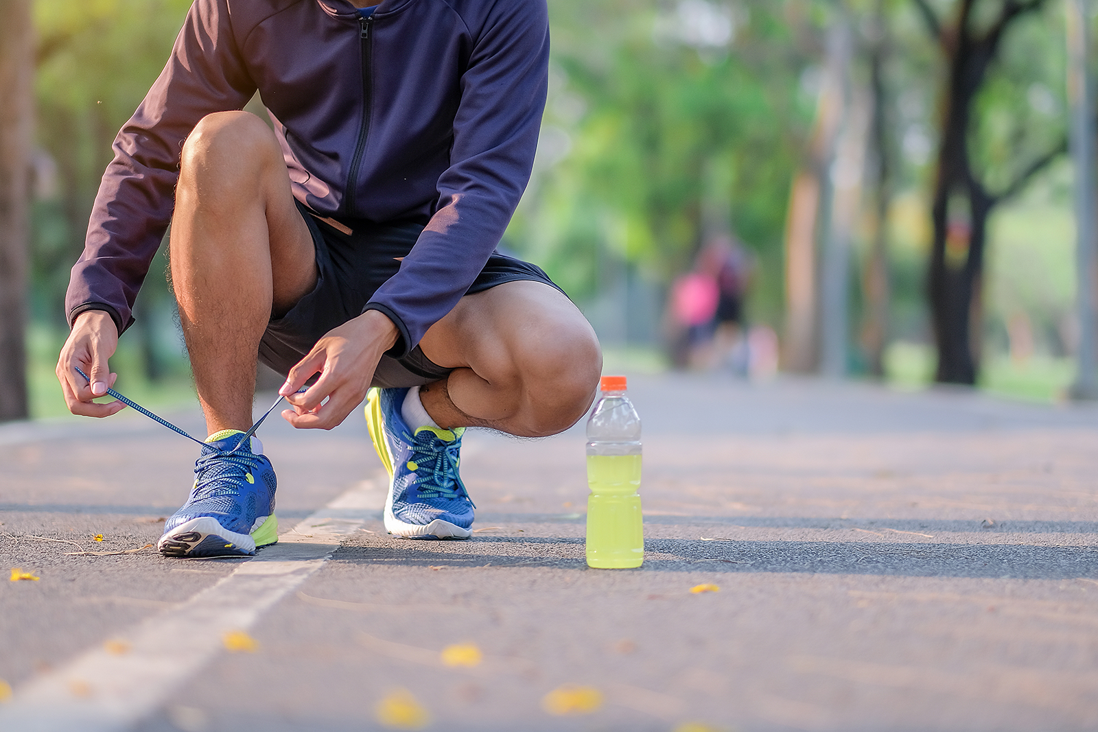 Male runner ties sneakers on a paved trail
